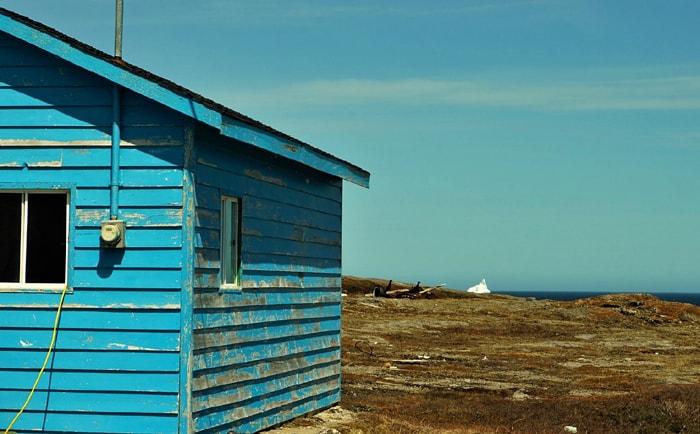 Maison bleue et iceberg à Terre-Neuve